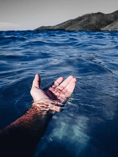Eine Hand, ausgestreckt im blauen Wasser, im Hintergrund die Küste als Symbolbild für das Forum Mut.